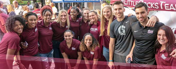 A happy, diverse group of UA Little Rock student athletes kick off the 2018-2019 UALR athletic season during a Trojan Day block party event in downtown Little Rock.