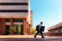Student walking past the Ottenheimer Library, Student Union A, and the Donaghey Student Center.