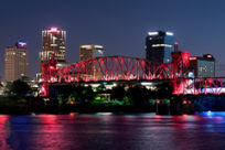 The downtown Little Rock skyline at night with the Junction Bridge covered in maroon lights.