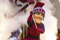 The UA Little Rock mascot, Maximus, running through a cloud of smoke with a Trojan flag at a basketball game.