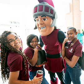 Three orientation leaders pose with the mascot inside the student center.