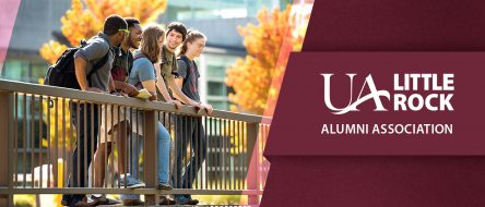 UA Little Rock Alumni Association logo overlaid on a photo of students smiling and talking on a bridge over the Coleman Creek.