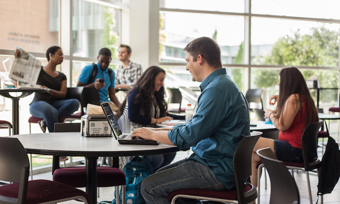 Students sitting in cafeteria using laptops