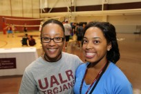 Two students in the fitness center smiling at camera, one wearing a UALR Trojans t-shirt