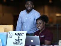 "Two smiling students behind sign ""parent and guest check-in"""