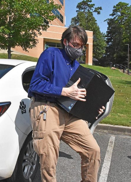 Student donating computer equipment