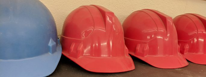 A blue hard hat with three red hard hats to the right of it. Hard hats are a staple of jobs in construction.