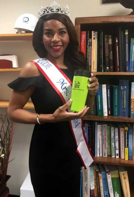 A photograph of Lashun Massey in black dress with Mrs. Little Rock sash and grown holding a lime green sustainability committee coffee mug.