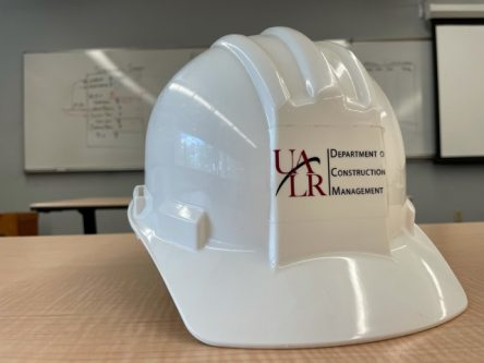 A white hard hat with the UA Little Rock logo sticker on it. The hat is in a classroom with writing on a whiteboard behind it.