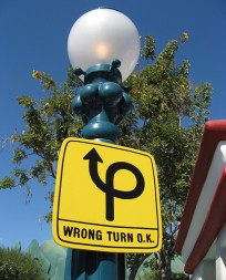 "yellow sign on light post saying ""wrong turn o.k."""