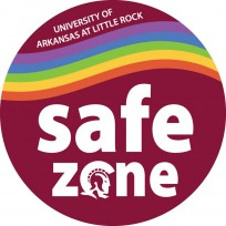 """Safe Zone logo is a round UA Little Rock """"maroon"""" background color. A rainbow stripe crosses the circle towards the top in a slightly wavy line. Above the rainbow line, in small white text, it reads """"UNIVERSITY OF ARKANSAS AT LITTLE ROCK."""" Below the line, the bulk of the circle is taken up with the words """"safe zone"""" printed in white. The """"o"""" in """"zone"""" is actually the Trojan mascot profile, also in white."""