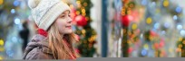 Young lady in knit snow hat with holiday decorations behind her.