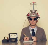A silly photo of a man wearing sunglasses and a colander on his head pretending to be a scientist.