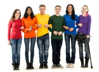Six young adults standing in a line with arms linked. Each person is wearing jeans a solid colored shirts, each in one of the standard rainbow colors. From left to right, the people are wearing shirts in red, orange, yellow, green, blue, and purple.