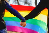 A young, blonde white woman in a royal blue sweater holds hands with a man in a black sweater in front of a rainbow flag outside on a crisp autumn day.