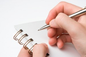 hands poised to take notes on paper