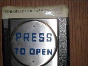 "Close-up photo of a button to press to open an automatic door. Above it is a note that reads ""for disabled patrons only."" Photo by Tawana Scott."