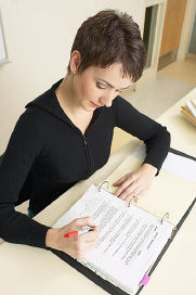 woman looking at 3-ring binder, holding a pen