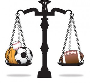 Sports Law Icon - Scales of justice holding sporting equipment