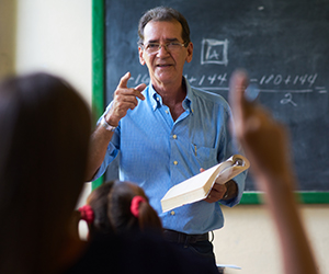Older male instructor answering questions at the front of a classroom.