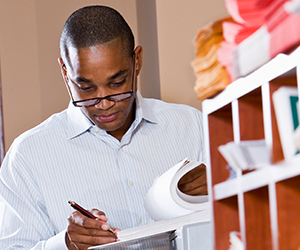 African American man standing next to faculty mailboxes as he reviews a document.