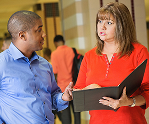 A woman holding an open binder discusses something with a male colleague in the hallway of a school.