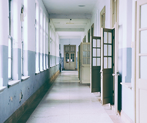 Well lit school hallway with open doors on the right and windows on the left.