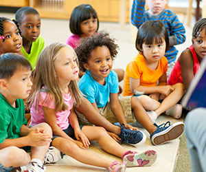 A teacher is reading a book to a group of very young students sitting in a semicircle.