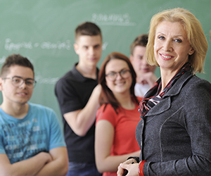Smiling older female teacher standing in front of a classroom. In the background there are students lined up and smiling.