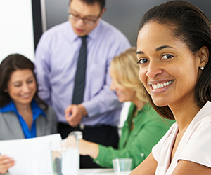 College administrative working together in a conference room with an African American woman in the foreground smiling at the camera.