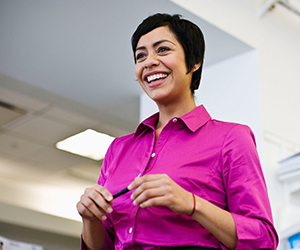 Photo of a smiling woman in a fuchsia button shirt standing in an office.