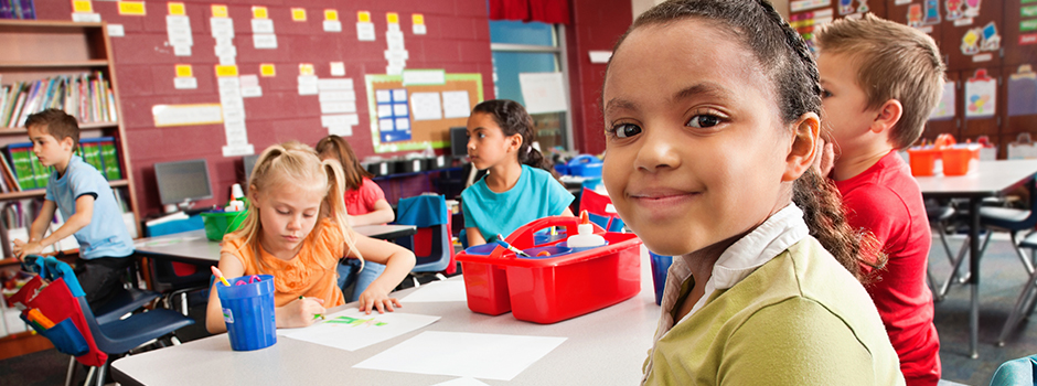 Students working in a classroom on an art related project. Young girl is in the foreground smiling at the camera.