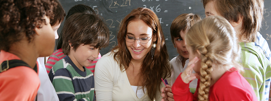 A group of middle school students are surrounding a young female teacher as she works on a math problem.