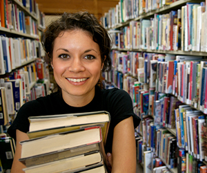 Woman smiling and holding books in the stacks at a library.