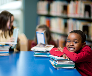 Young adolescent children sitting at a table in a library reading books. There is an African American boy in the foreground smiling at the camera and leaning on a stack of books.
