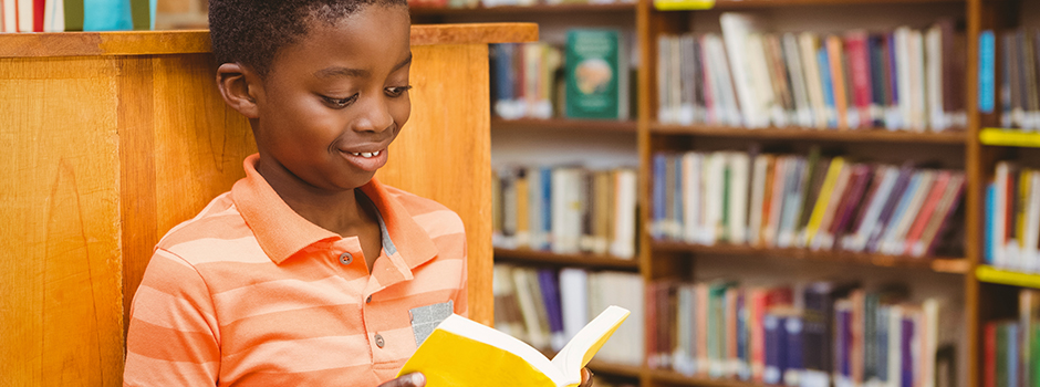 A young African American boy smiles while reading a book as he leans against a short bookcase.