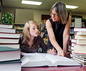 Older woman and female student surrounded by stacks of books as they work on research in a library.
