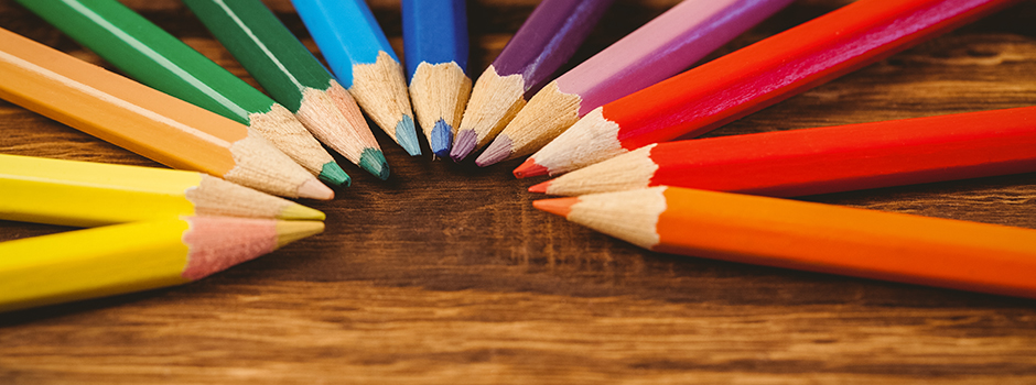 Yellow, green, blue, purple, red, and orange colored pencils arranged in a semi-circle on a wooden table top.