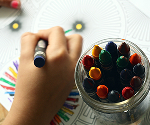 Child using crayons to color a sheet with geometric shapes.