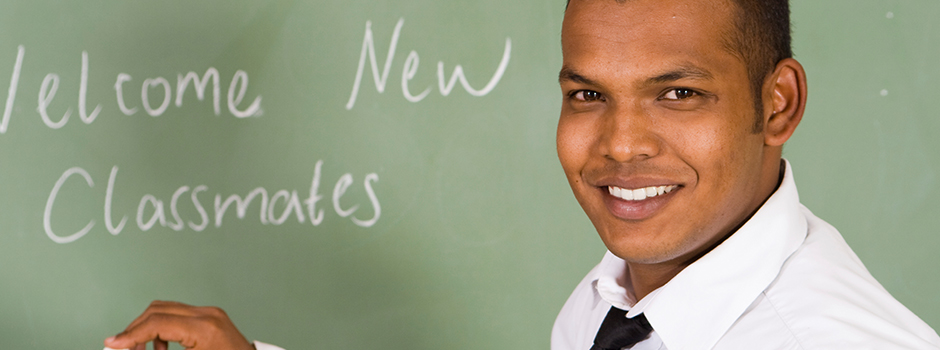 Hispanic male teacher standing in front of a chalkboard with the text welcome new classmates.
