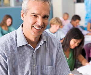 Close up of a male teacher smiling at the camera and there are students working in the background.