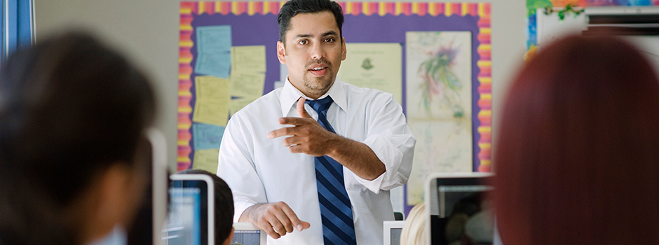 Young hispanic male teaching in front of a classroom of students sitting at computers.