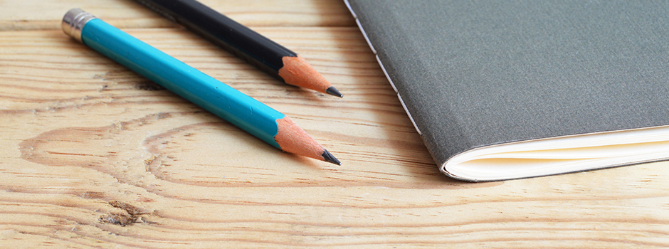 Up close image of a grey notebook and two pencils on a wooden table.