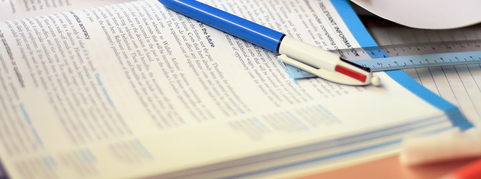 A pen and ruler sit on the righthand page of an open textbook surrounded by notebook paper on a desk.
