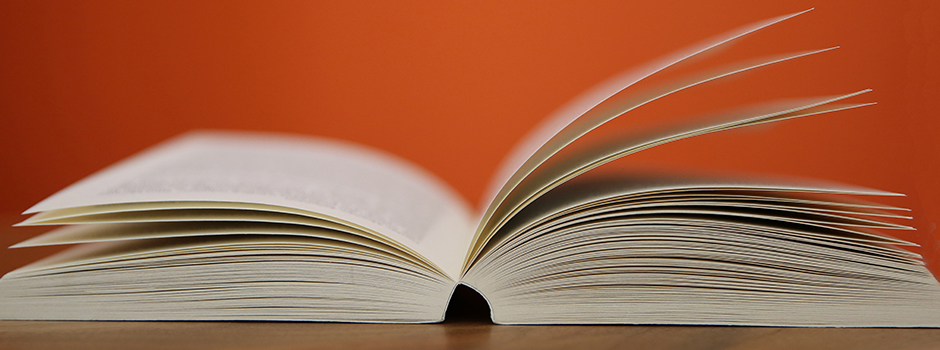 Open book on a wooden table with an orange background.