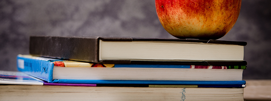 An apple sitting on a stack of books in front of a chalkboard.