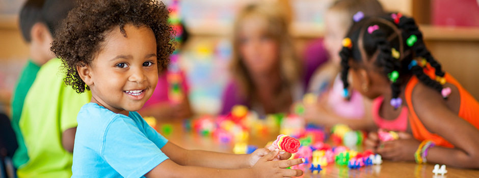 Image of young children building with colorful blocks in a classroom. Child in the foreground is smiling and looking at the camera.