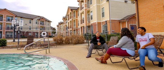 Three students relax by the pool at the University Village Apartments.
