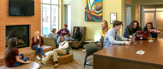 Ten freshman students hang out in the lobby of West Hall.