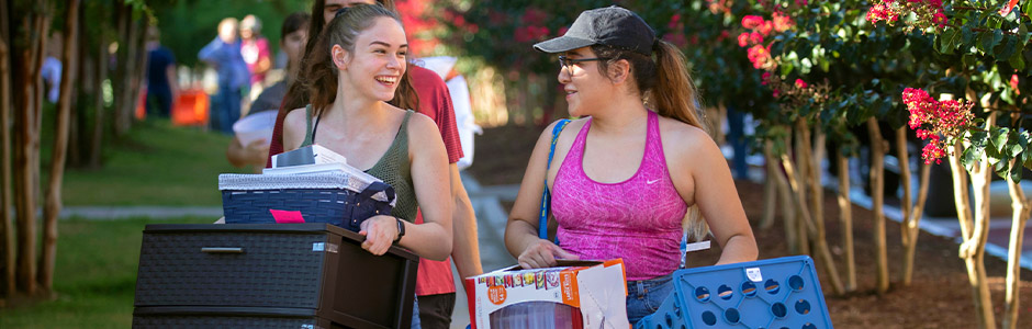 Two students laughing together while carrying boxes into a residence hall on move-in day.